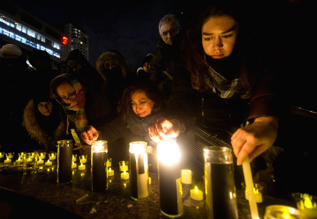 People pay their respect during a candlelight vigil to honor victims of the Ukrainian passenger plane crash at Mel Lastman Square in Toronto, Canada, Jan. 9, 2020. ...