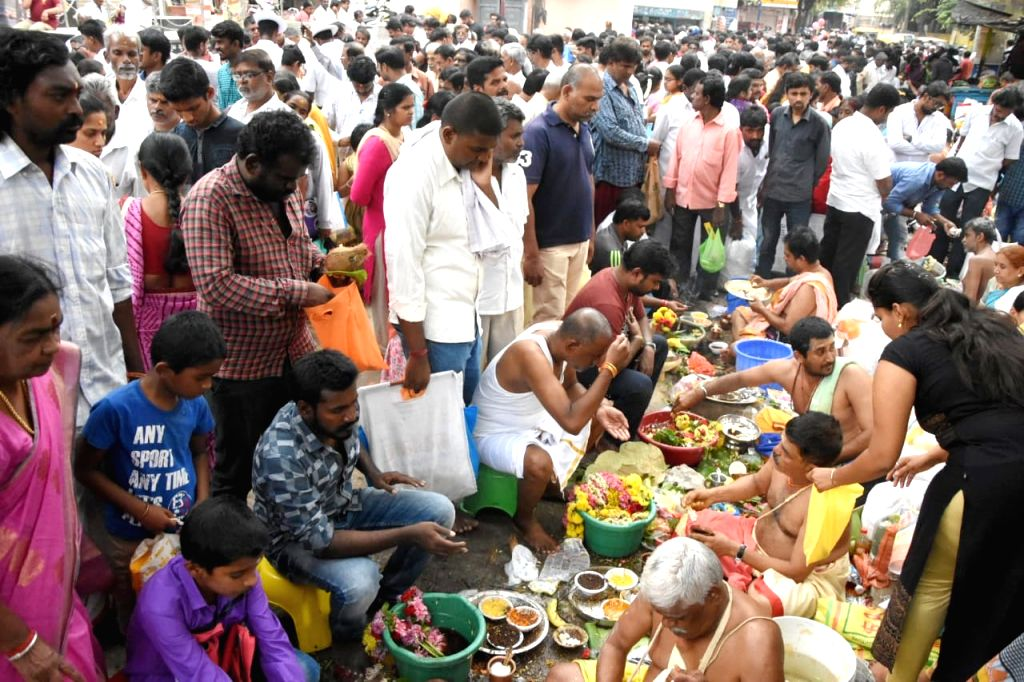 People perform rituals as they offer 'tarpan' to pay tributes to their ancestors on the occasion of Mahalaya Amavasya at Kashi Vishwanath Temple, Chickpet in Bengaluru on Sep 28, 2019.
