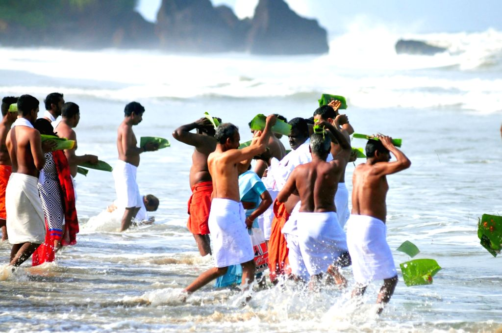 People perform rituals at the Payyambalam beach on the occasion of Karkidaka Vavu Bali in Kannur on Aug 2, 2016.
