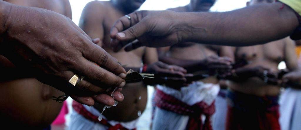 People perform rituals on the banks of the Hooghly River on Mahalaya in Kolkata, on Sept 29, 2016.