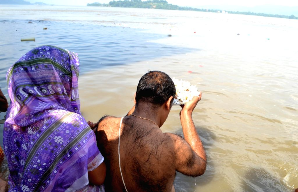 People perform rituals on the banks of the Brahmaputra River on Mahalaya in Guwahati on Sept 30, 2016.