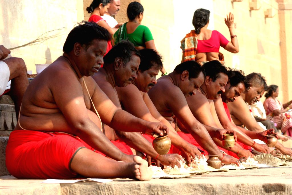 People perform rituals on the banks of the Ganga river as `Pitripaksha`- a 16-day period when Hindus pay homage to their forefathers, begins in Varanasi on Sept 9, 2014.