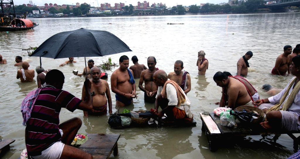 People perform 'tarpan' - a ritual in the Vedic practice - on the bank of Ganga on occasion of Mahalaya in Kolkata on Sep 19, 2017.