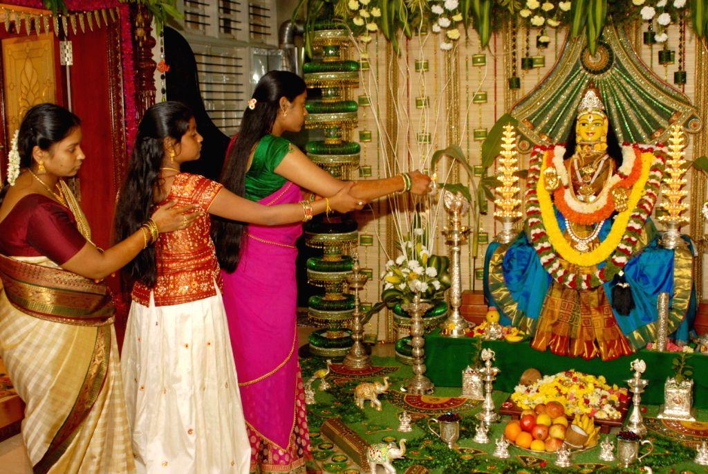 People performing pooja to goddes Varamahalakshmi on the occasion of Karnataka traditional festival Varamahalakshmi fest in Bengaluru on August 16, 2013. (Photo::: IANS)