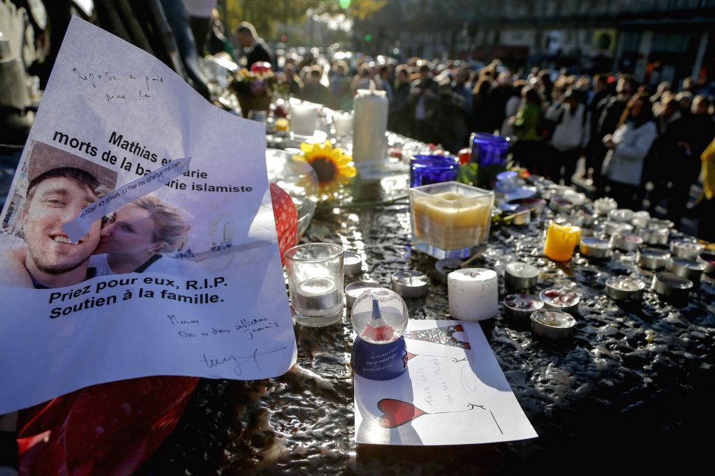 People place flowers and candles at the Place de la Republique square to mourn for the victims of the terrorist attacks in Paris, capital of France, Nov. 15, 2015. ...