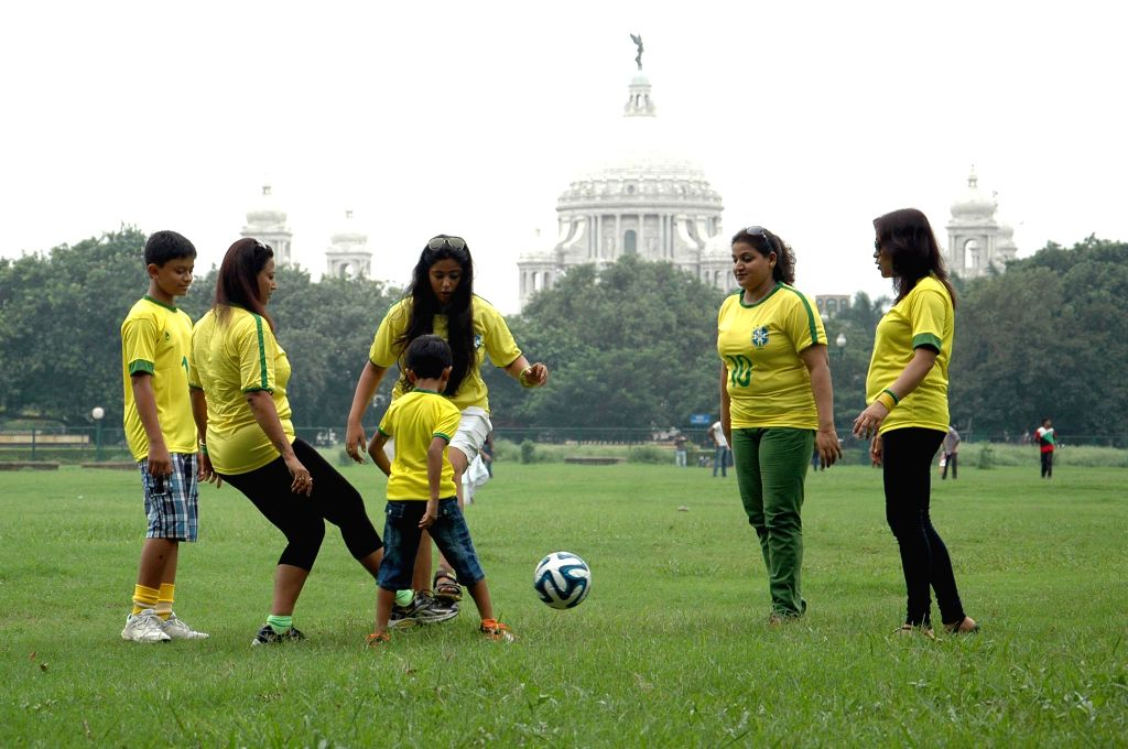 People play football wearing jersey of Brazilian football team at Maidan in Kolkata on June 22, 2014.