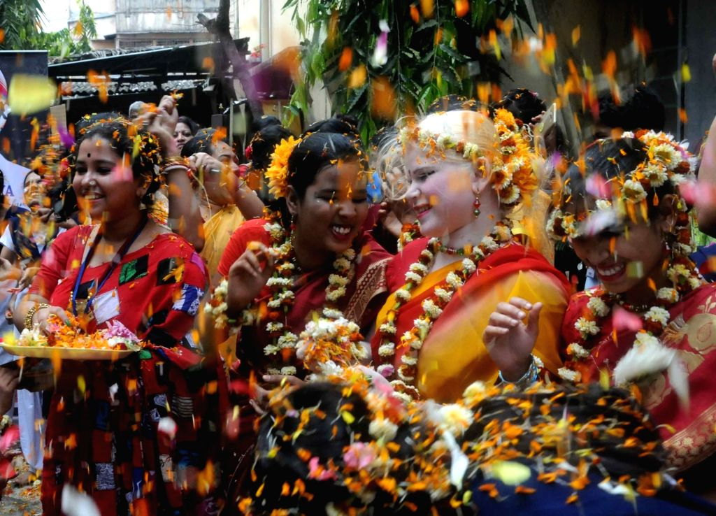 People play 'Holi' with flowers ahead of Holi in Kolkata on March 11, 2017.