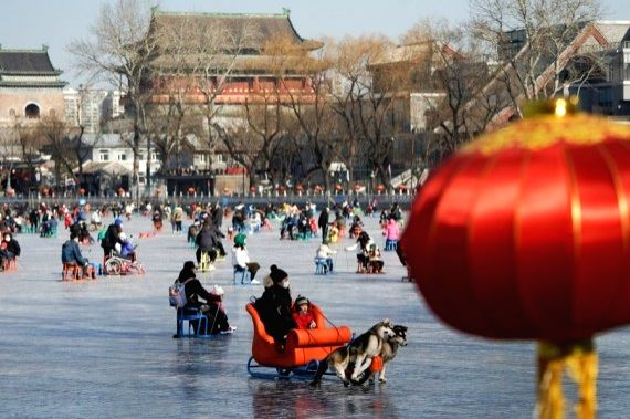 People play on the ice-covered Shichahai lake which has been turned to an ice rink in Beijing, capital of China, Jan. 17, 2021.