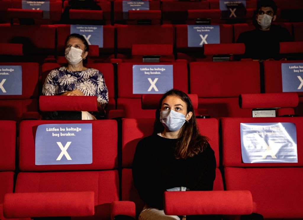 People practice physical distancing while watching a film during the Istanbul Film Festival in Istanbul, Turkey, on Oct. 13, 2020. Due to the COVID-19 pandemic, ...