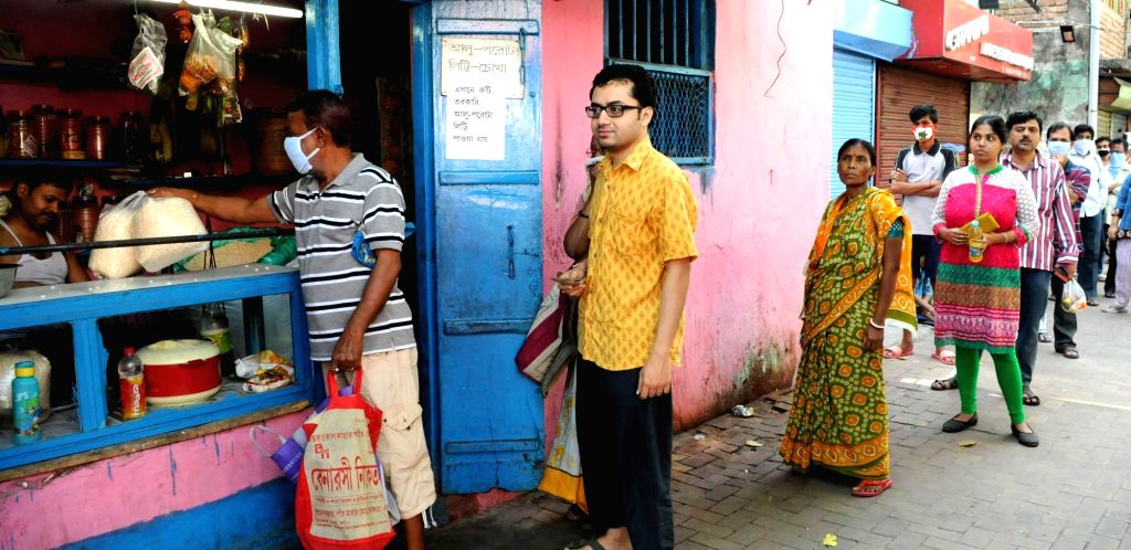 People practise social distancing as they queue up to buy essential commodities outside a general store on Day 5 of the 21-day countrywide lockdown imposed to contain the spread of novel ...