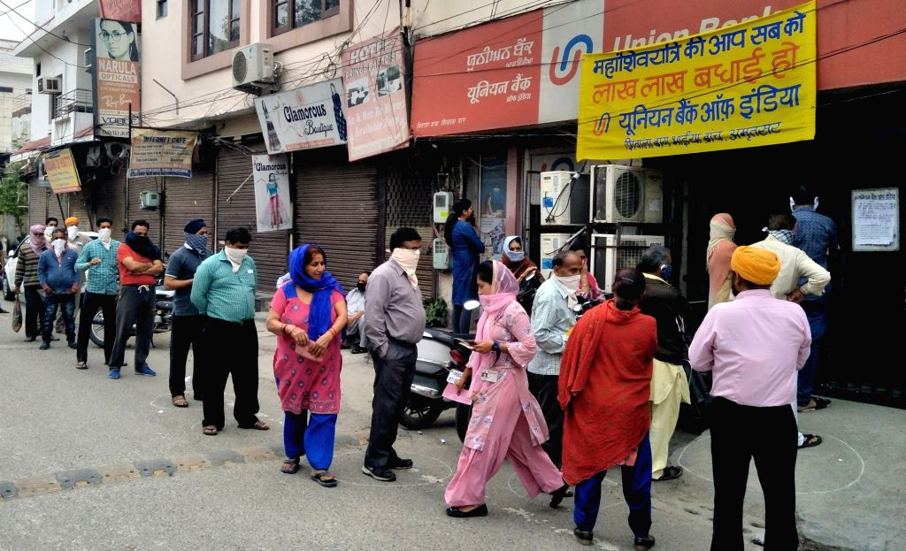 People practise social distancing as they queue up outside an ATM on Day 6 of the 21-day countrywide lockdown imposed to contain the spread of novel coronavirus, in Amritsar on March 30, ...