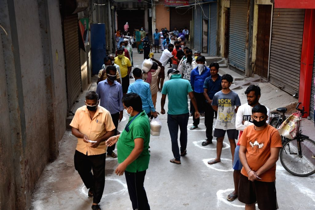 People practise social distancing as they queue up to collect foodgrains being distributed among the poor, needy and homeless people in Patna during the extended nationwide lockdown imposed to ...