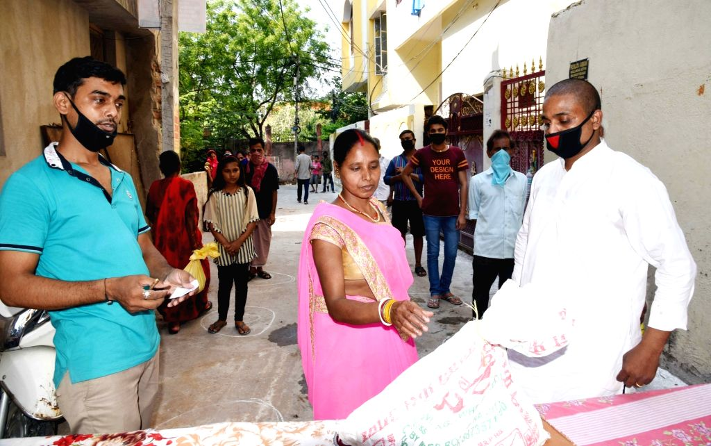 People practise social distancing as they queue up to receive food and other essentials being distributed among the poor, needy and homeless people in Patna during the extended nationwide ...