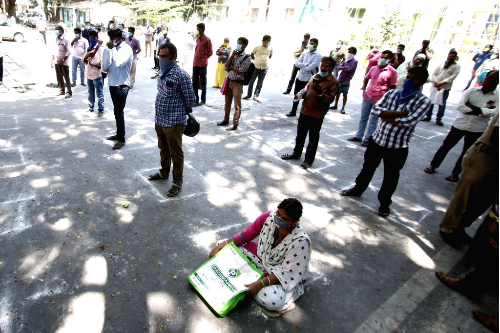 People practise social distancing as they wait in multiple queues to collect inter-state travel passes being issued by the Corporation of Chennai, during the 21-day nationwide lockdown (that ...