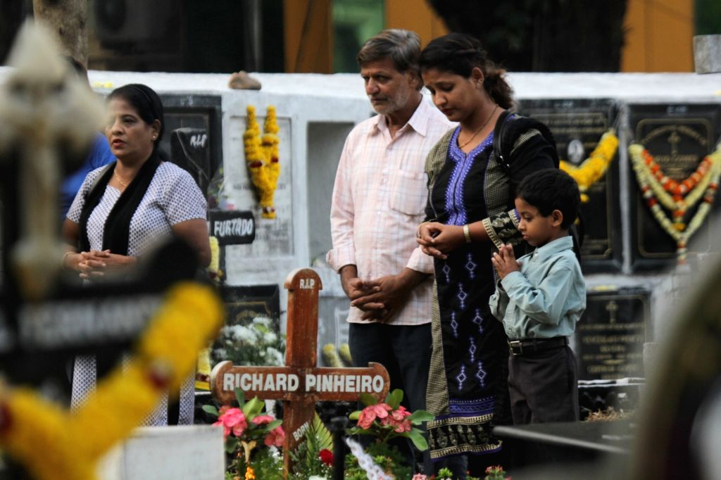 People pray at the grave of their deceased relatives on All Souls Day in Panaji, on Nov 2, 2015.