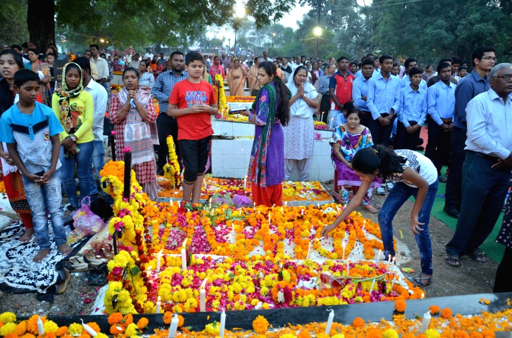 People pray at the graves of her relative at a cemetery on All Souls' Day in Bhopal, on Nov 2, 2018.
