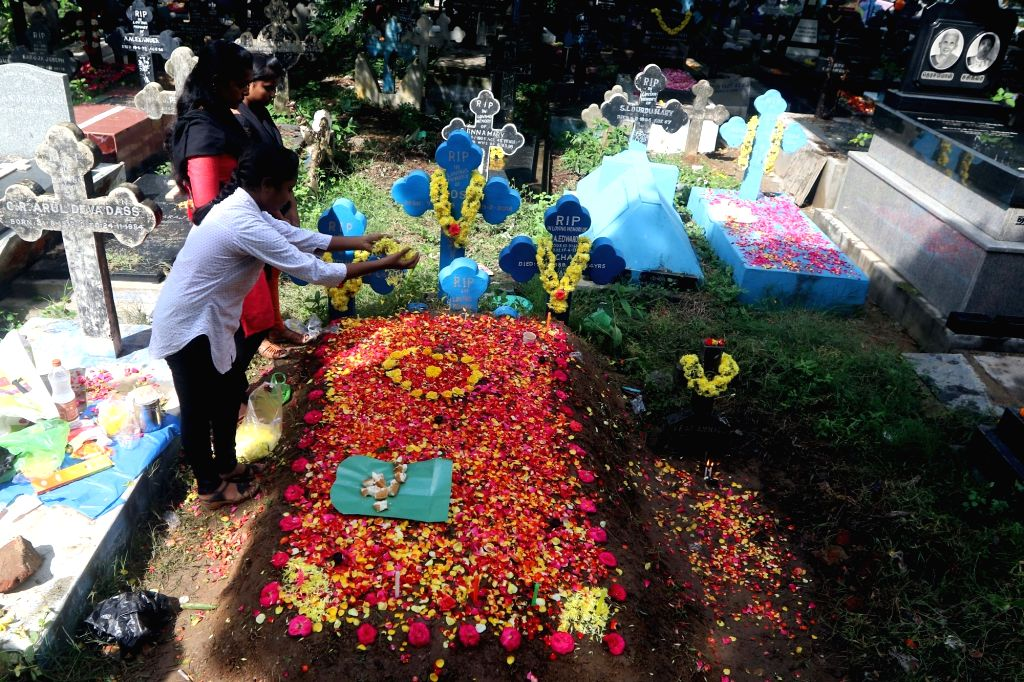 People pray besides the grave of their relatives at a cemetery during the observance of All Souls' Day in Chennai, on Nov 2, 2018.