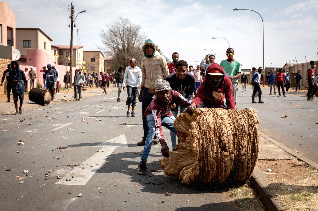 People prepare to barricade a road during a protest over the death of a teenager in Eldorado Park, Johannesburg, South Africa, Aug. 27, 2020. South African ...