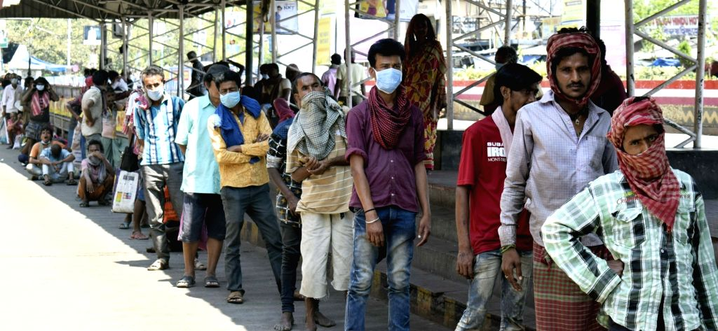People queue up during food distribution by the Railway Protection Force to the poor, homeless and needy on Day 5 of the 21-day countrywide lockdown imposed to contain the spread of novel ...