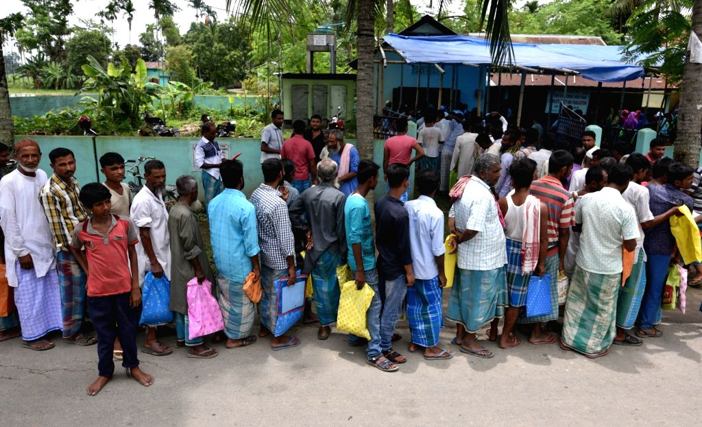 People queue up outside a NCR Seva Kendra in Nagaon to check their name on the first complete draft of the National Register of Citizens (NRC) that was published on July 30, 2018 and ...