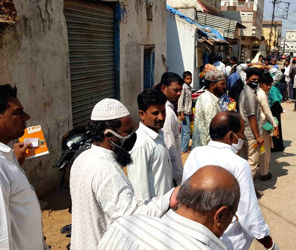 People queue up outside a ration shop on Day 2 of the 21-day nationwide lockdown imposed by the Narendra Modi government over the coronavirus pandemic; in Hyderabad on March 26, 2020. - Narendra Modi