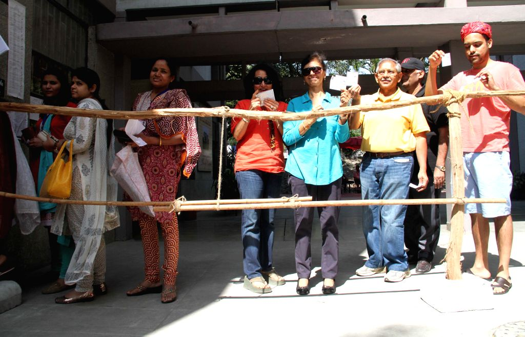 People queue-up to cast their votes at a polling booth during the third phase of 2014 Lok Sabha Polls in New Delhi on April 10, 2014. Elections are being held in 91 parliamentary constituencies of ...