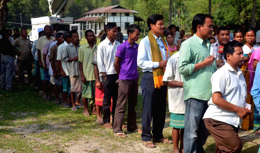 People queue-up to cast their votes at a polling booth during the sixth phase of 2014 Lok Sabha Polls in Kokrajhar of Assam on April 24, 2014.