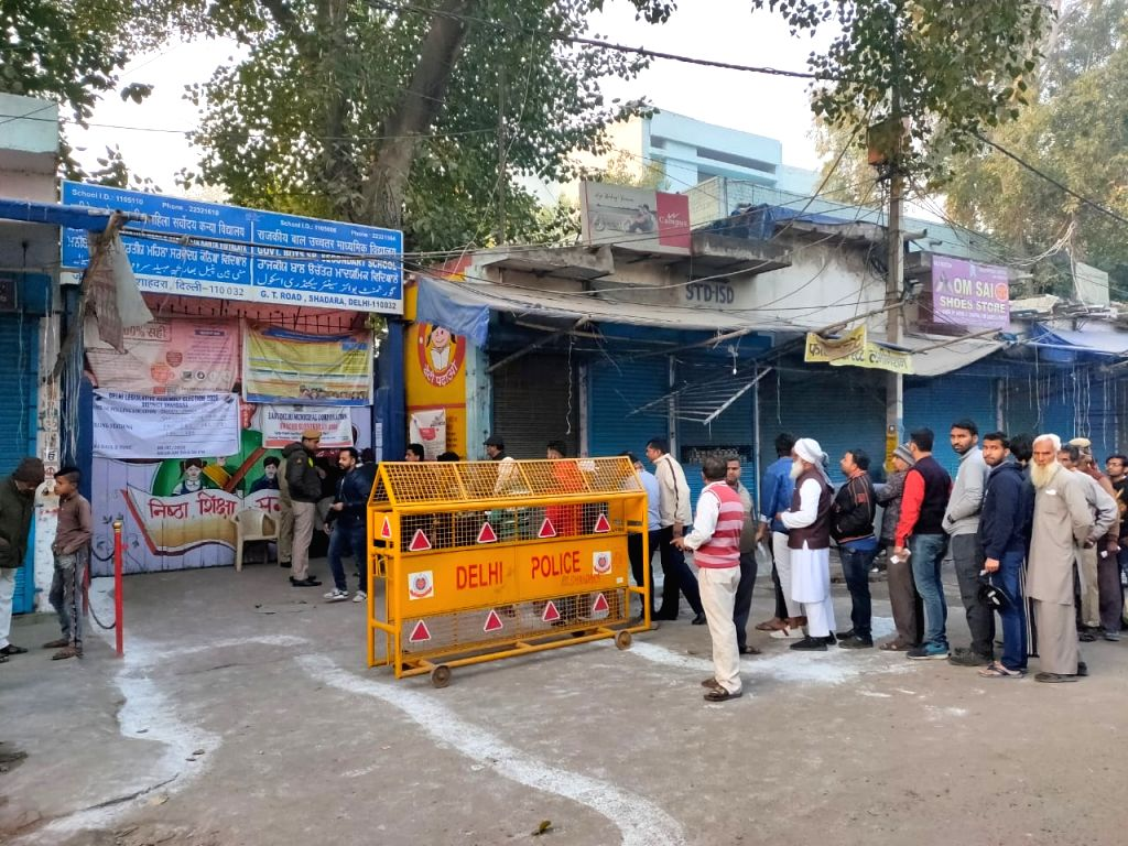 People queue up to cast their votes for the Delhi Assembly elections 2020, at a polling station at Delhi's Shahdara on Feb 8, 2020.