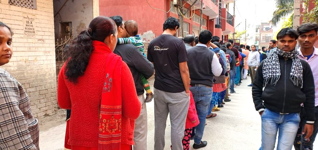 People queue up to cast their votes for the Delhi Assembly elections 2020, at a polling station at Delhi's Dwarka on Feb 8, 2020.