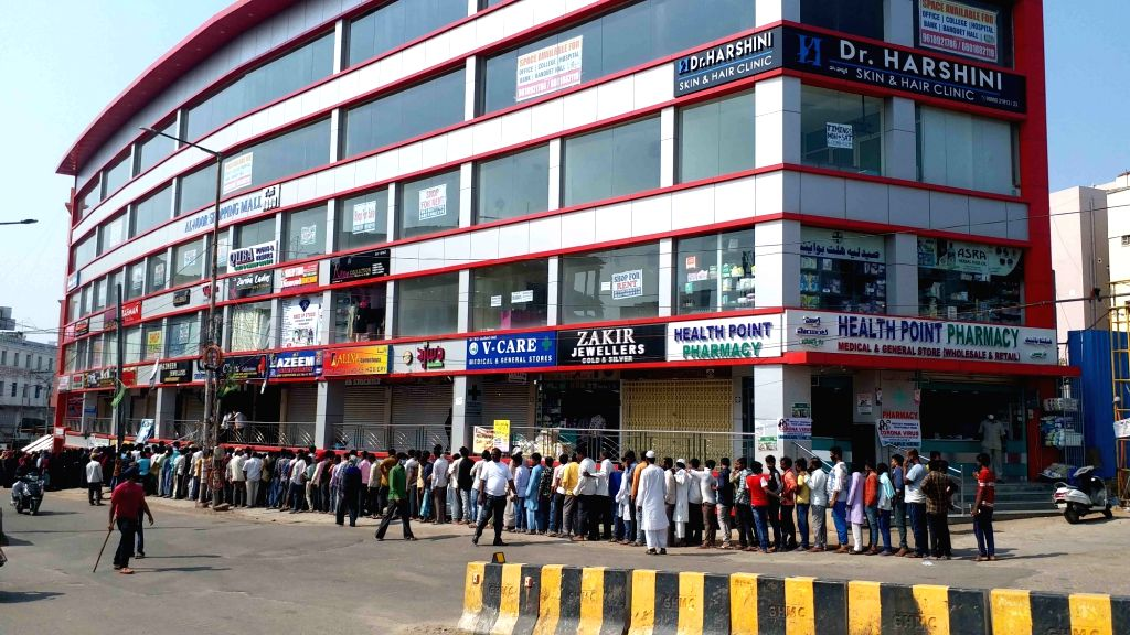 People queue up to collect essential commodities being distributed free of cost by social workers on Day 7 of the 21-day nationwide lockdown imposed as a measure to contain the spread of  ...