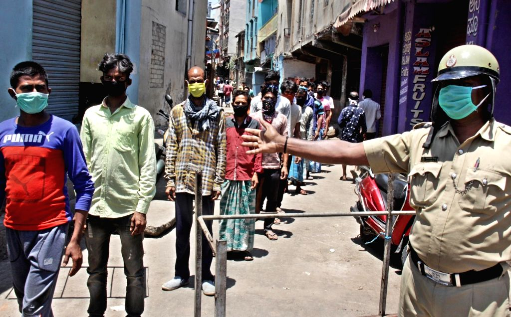 People queue up to collect food during free food distribution on Day 6 of the 21-day countrywide lockdown imposed to contain the spread of novel coronavirus, in Bengaluru on March 30, 2020.