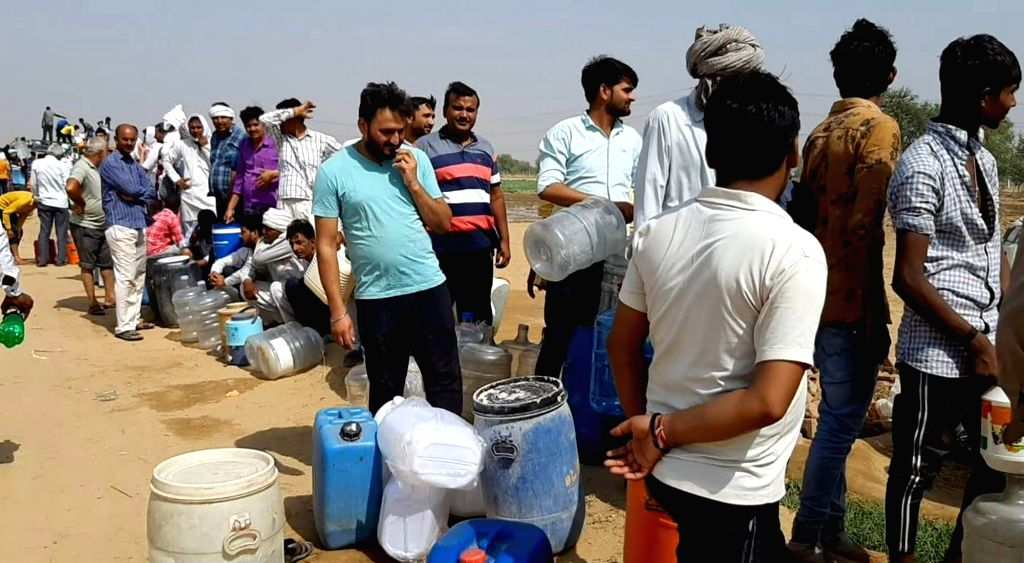 People queue up to collect 'miracle' water that they believe is a panacea for several diseases, including diabetes, at Gujriwas village in Haryana's Rewari district, on June 7, 2019. Hundreds ...