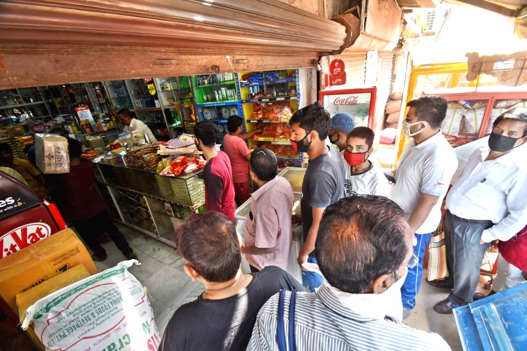 People queue up to purchase groceries at a general store on Day 2 of the 21-day nationwide lockdown imposed by the Narendra Modi government over the coronavirus pandemic; in Patna on March 26, ... - Narendra Modi