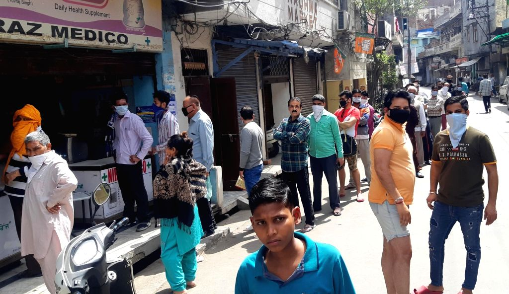 People queue up while practising social distancing outside a medical store on Day 2 of the 21-day nationwide lockdown imposed by the Narendra Modi government over the coronavirus pandemic; ... - Narendra Modi