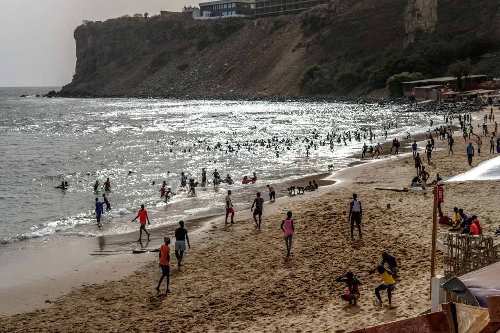 People relax on a beach in Dakar, Senegal, on July 1, 2020. Four months after the outbreak of the COVID-19 pandemic on March 2 in Senegal, the country's confirmed ...