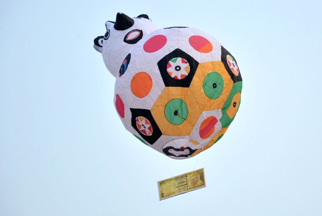 People release hot air balloon with a replica of old currency note of Rs 500 attached to it in Kolkata on Nov 27, 2016.