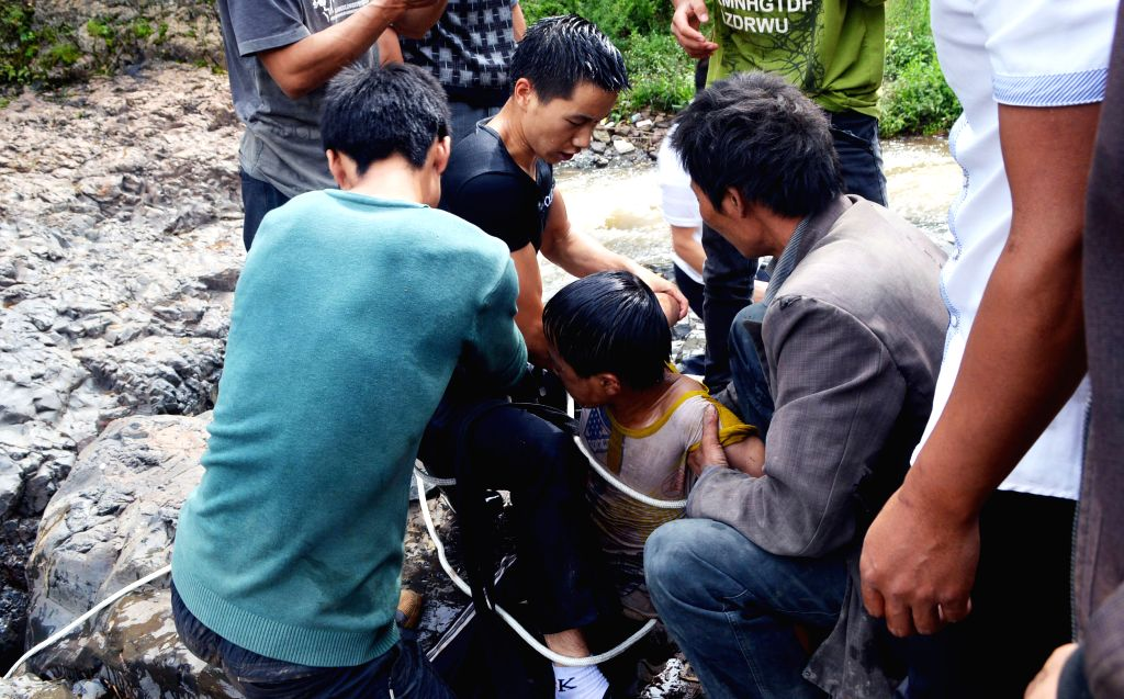 People rescue a boy at Diaoshui Village of Mazha Town in Weining County, southwest China's Guizhou Province, Aug. 16, 2015. The boy was washed down the waterfall ...