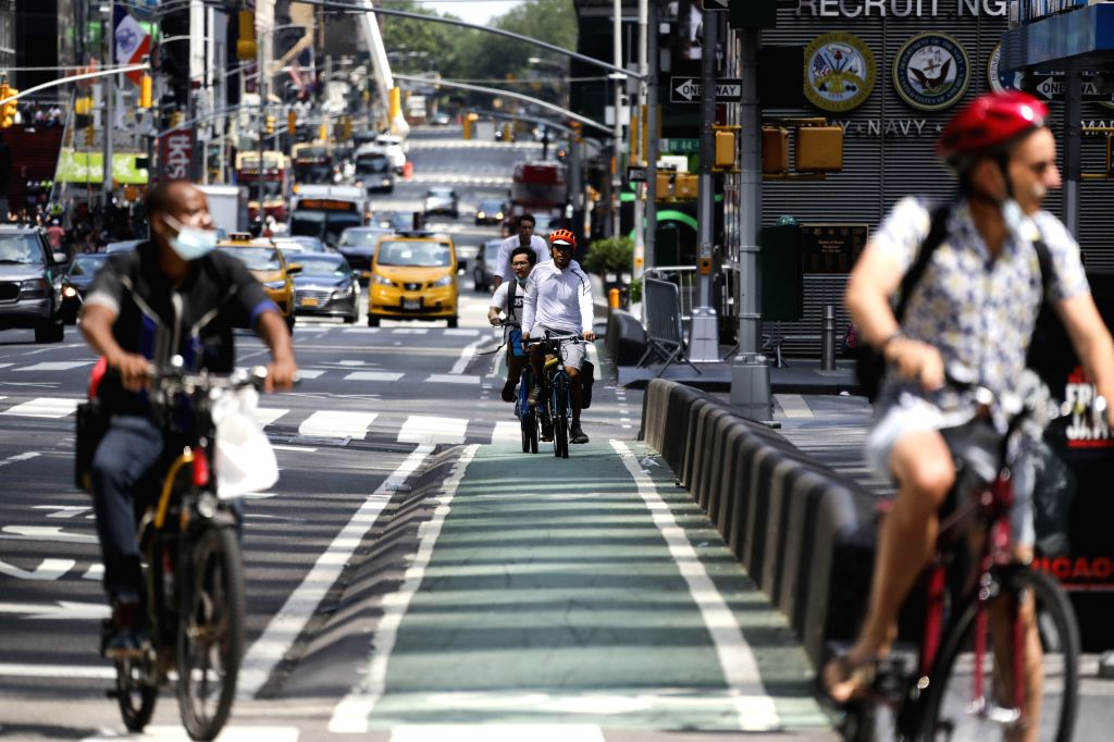 People ride bikes in Times Square in New York, the United States, on Aug. 9, 2020. The total number of COVID-19 cases in the United States surpassed the 5 million ...