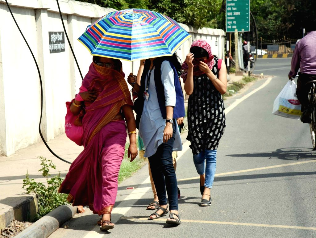 People shield themselves from the scorching sun on a hot day in Patna, on April 15, 2019.