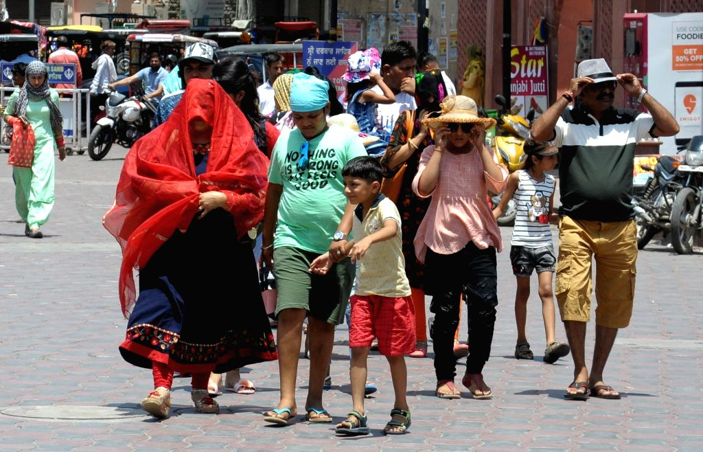 People shield themselves from the scorching sun on a hot sunny day, in Amritsar on May 31, 2019.
