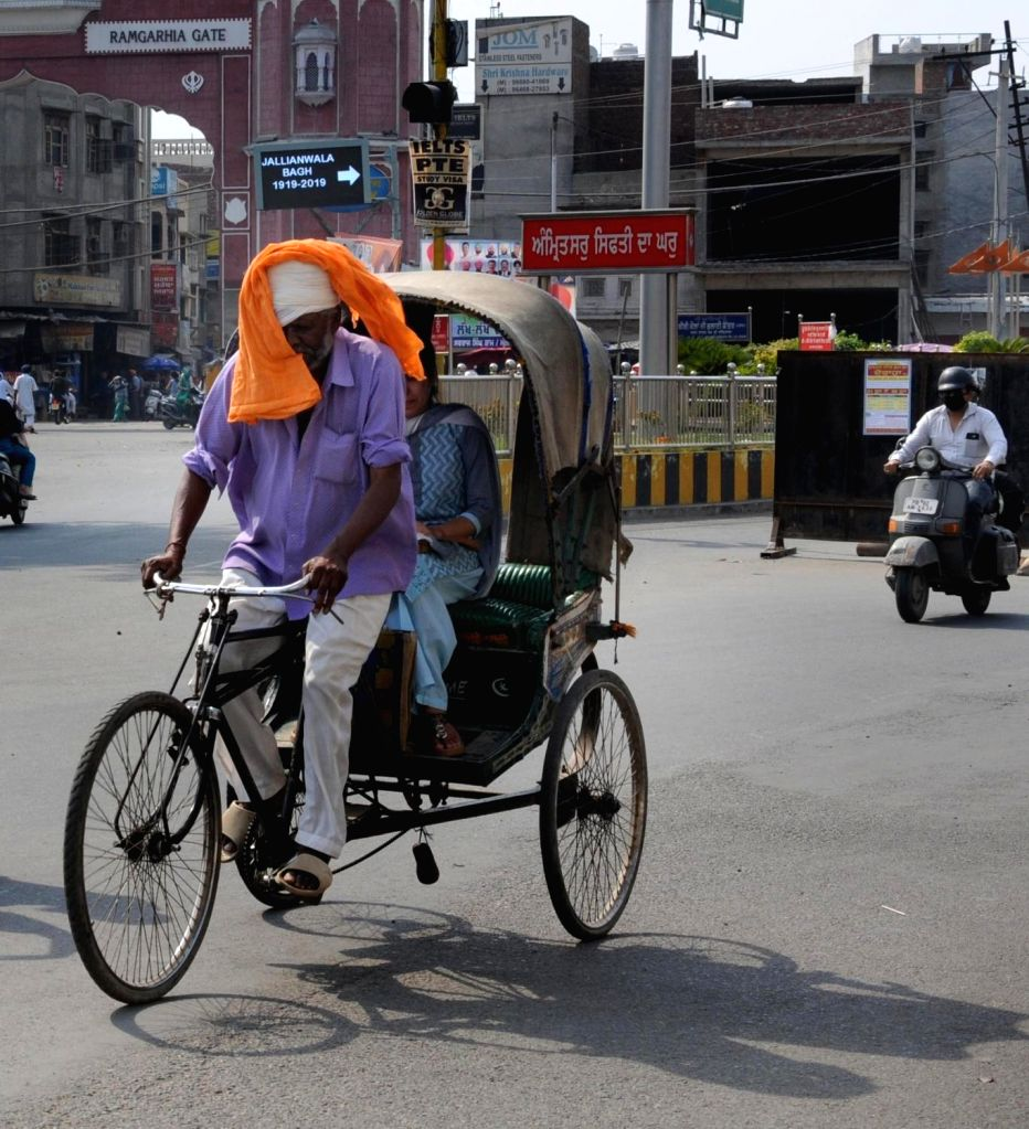 People shield themselves from the scorching sun as the temperatures soar to 44 degrees in Amritsar, on June 1, 2019.