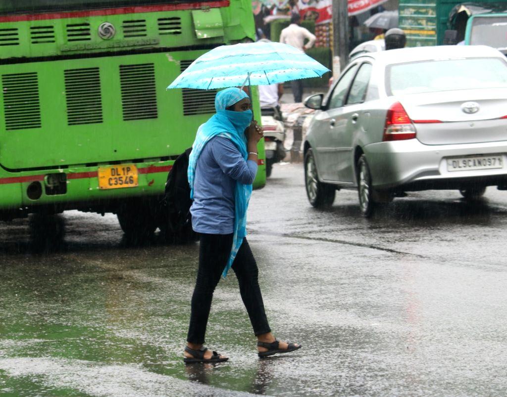People shield themselves using umbrellas as rains lash New Delhi on Aug 13, 2020.