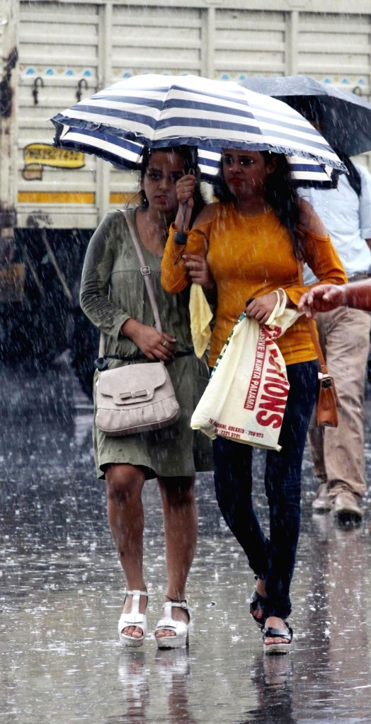 People shield themselves with umbrellas as rains lash Kolkata on July 31, 2018.