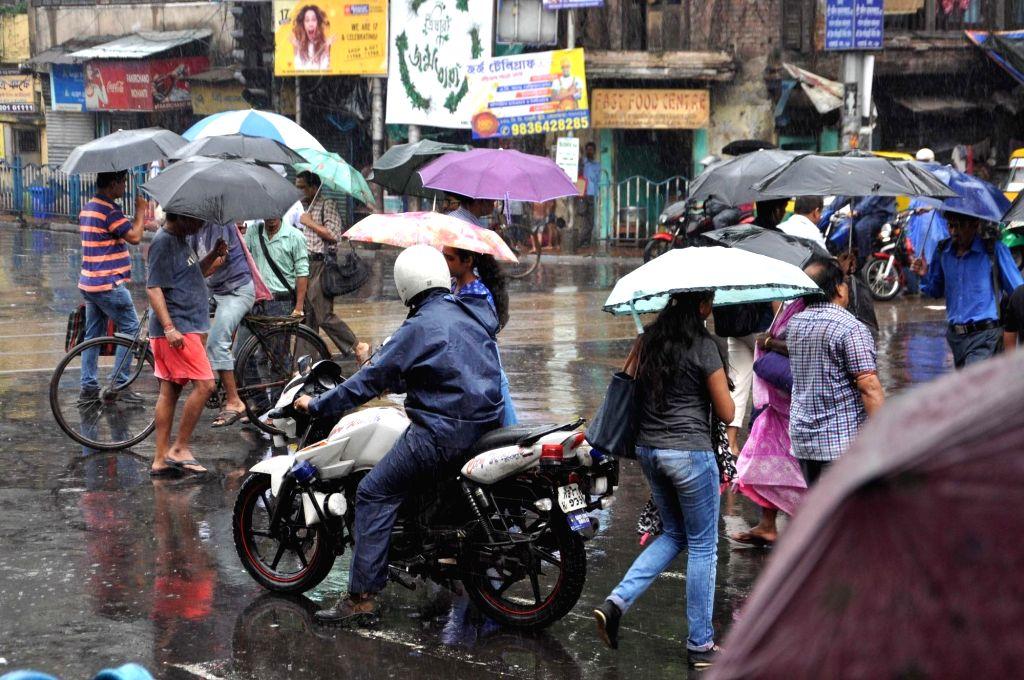 People shield themselves with umbrellas as rains lash Kolkata, on Aug 1, 2018.