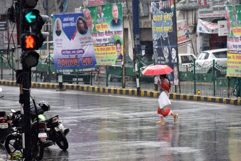 People shield themselves with umbrellas during rains in Patna on July 10, 2020.