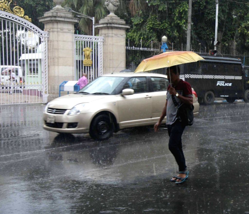 People shield themselves with umbrellas during rains, in Kolkata on May 31, 2018.