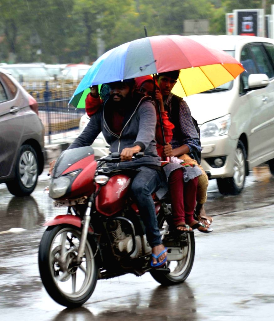 People shield themselves with umbrellas during rains, in Hyderabad on July 14, 2018.