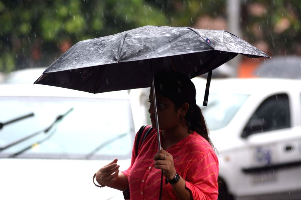 People shield themselves with umbrellas during rains, in Kolkata on July 16, 2019.