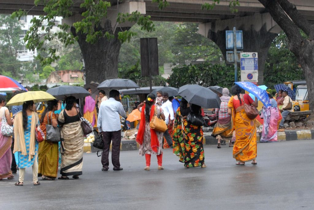 People shield themselves with umbrellas during rains, in Hyderabad on Aug 5, 2019.