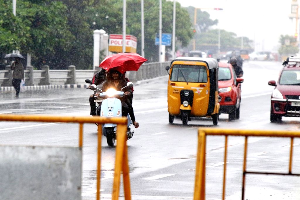 People shield themselves with umbrellas during rains, in Chennai on Oct 17, 2019.